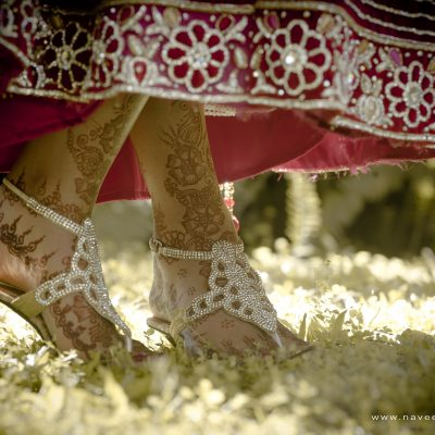 Close up of Indian bride's shoes dancing on green grass